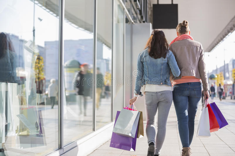 Rear view of young female friends with shopping bags walking on sidewalk by store royalty free stock photos