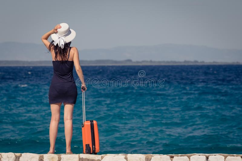 Female tourist with suitcase standing by the sea. Travel and sum stock images