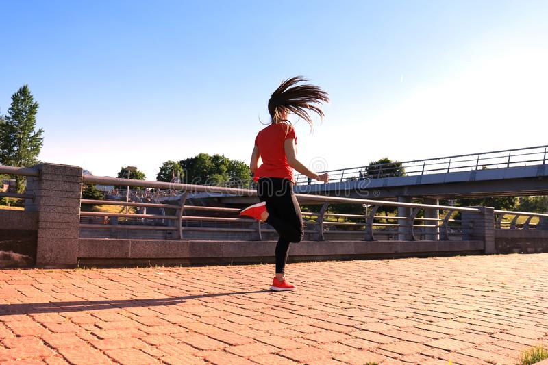 Rear view of young fitness woman wearing sports clothing exercising outdoors royalty free stock images