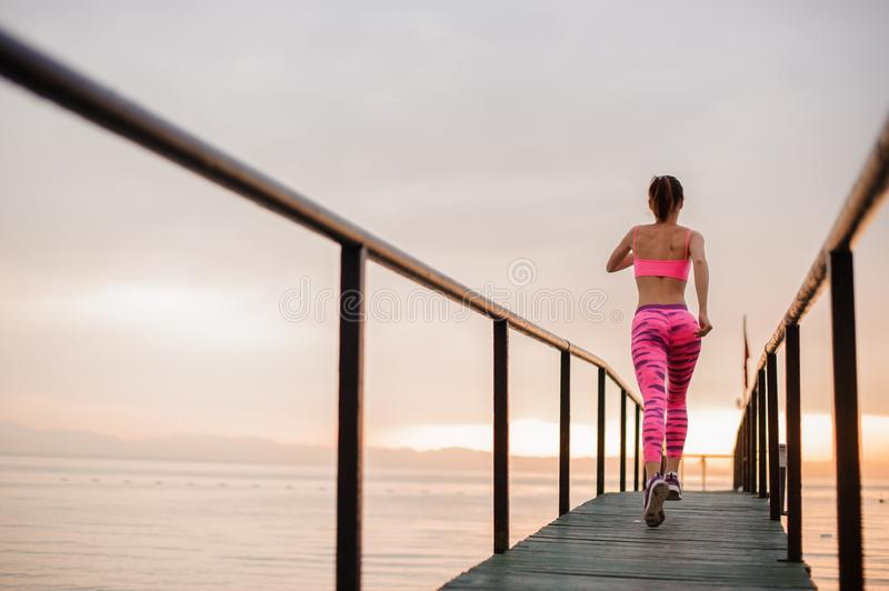 Rear view young girl running to the new life on the sunrise. Ready to achieve a new goal. Conception of the healthy lifestyle stock image