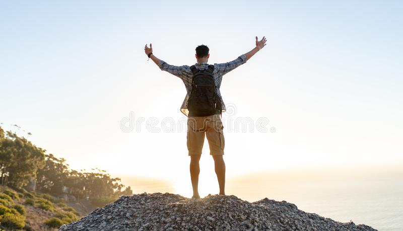 Rear view of young guy with backpack standing on the top of hill with arms spread open. Man enjoying the view from the top of the stock photos