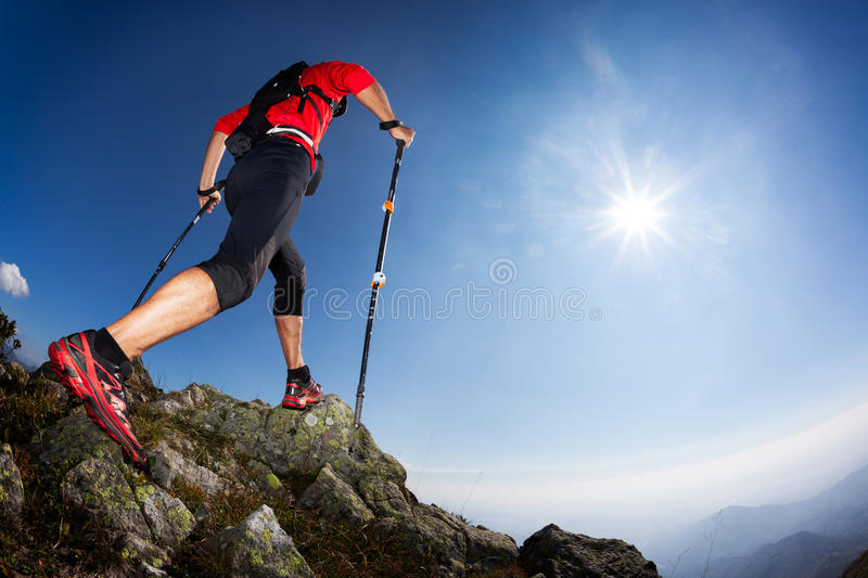 Rear view of a young male runner walking along a mountain trail royalty free stock photo