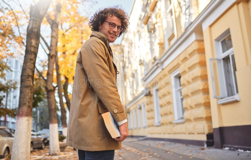 Rear view of young man with glasses posing with book outdoors. College male student carrying books in campus in autumn street. Smiling guy wears spectacles and stock photo