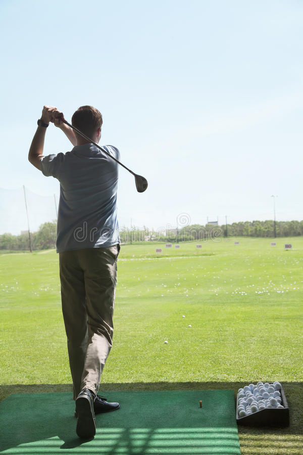 Download Rear View Of Young Man Hitting Golf Balls On The Golf Course, Arms Raised Stock Image - Image: 33399969