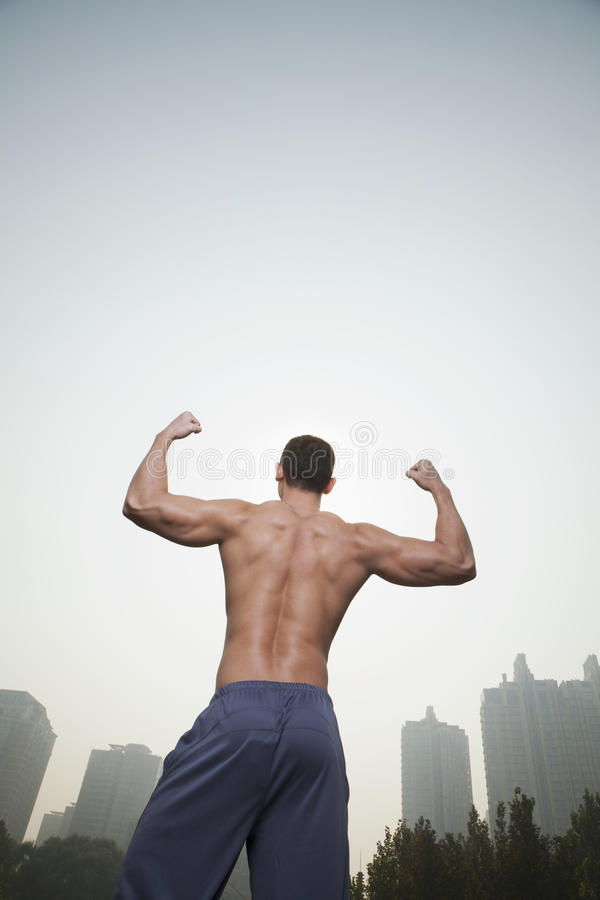 Rear View Of Young, Muscular Man With No Shirt On Flexing His Back Muscles, Outdoors In Beijing, China Royalty Free Stock Photography