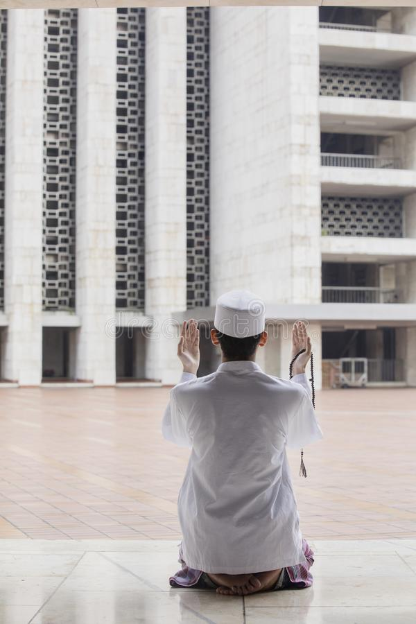 Young Muslim man praying to the Allah royalty free stock photo