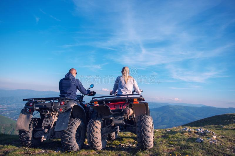 Rear view of young pair near atv. Man is showing something in distance to her girlfriend. stock photography