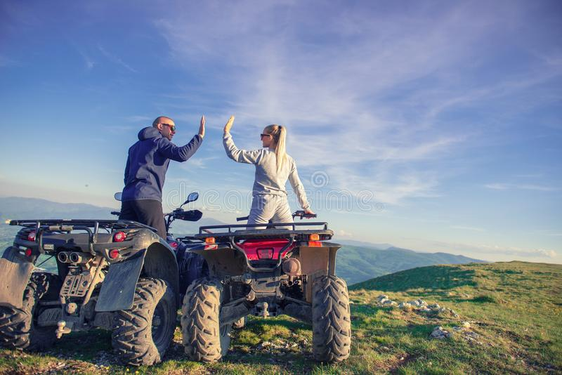 Rear view of young pair near atv. Man is showing something in distance to her girlfriend. royalty free stock photo