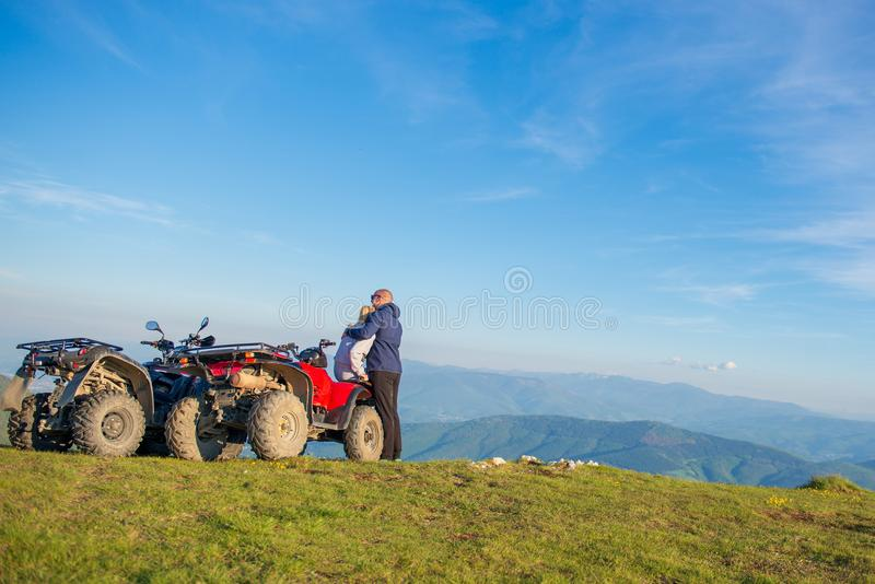 Rear view of young pair near atv. Man is showing something in distance to her girlfriend. royalty free stock image