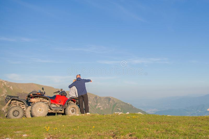Rear view of young pair near atv. Man is showing something in distance to her girlfriend. royalty free stock photography