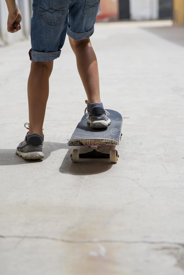 Rear view of young skateboarder legs riding on skateboard stock images