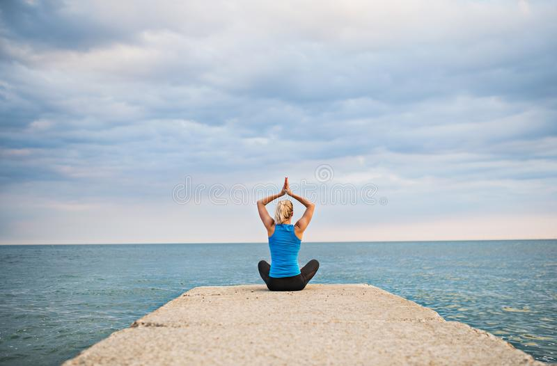 Rear view of a young sporty woman doing yoga exercise by the ocean outside. stock photography