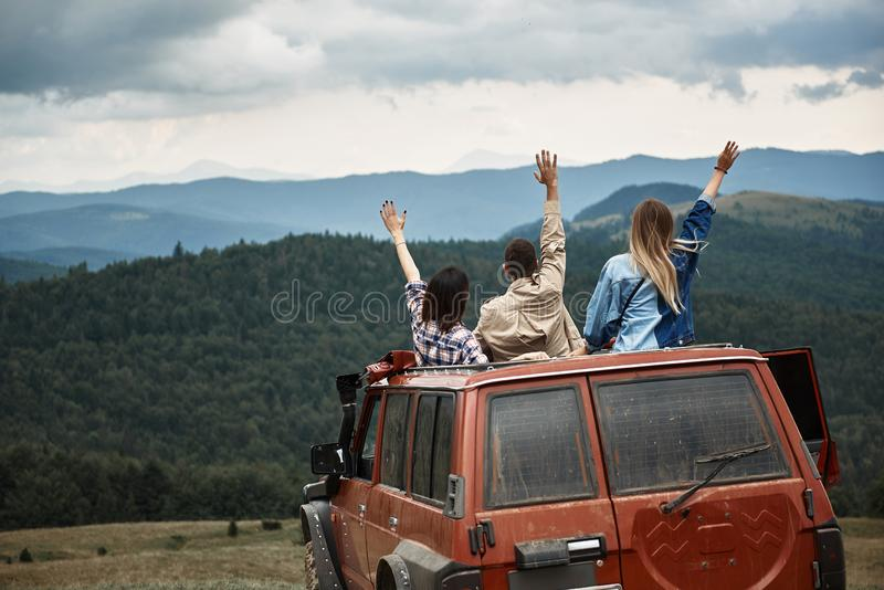 Rear view of young travelers spending weekend in the mountains stock photo