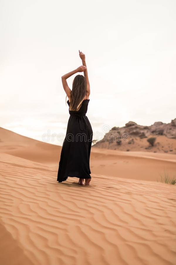 Rear view of young woman in black dress dancing in sandy desert at sunset royalty free stock image