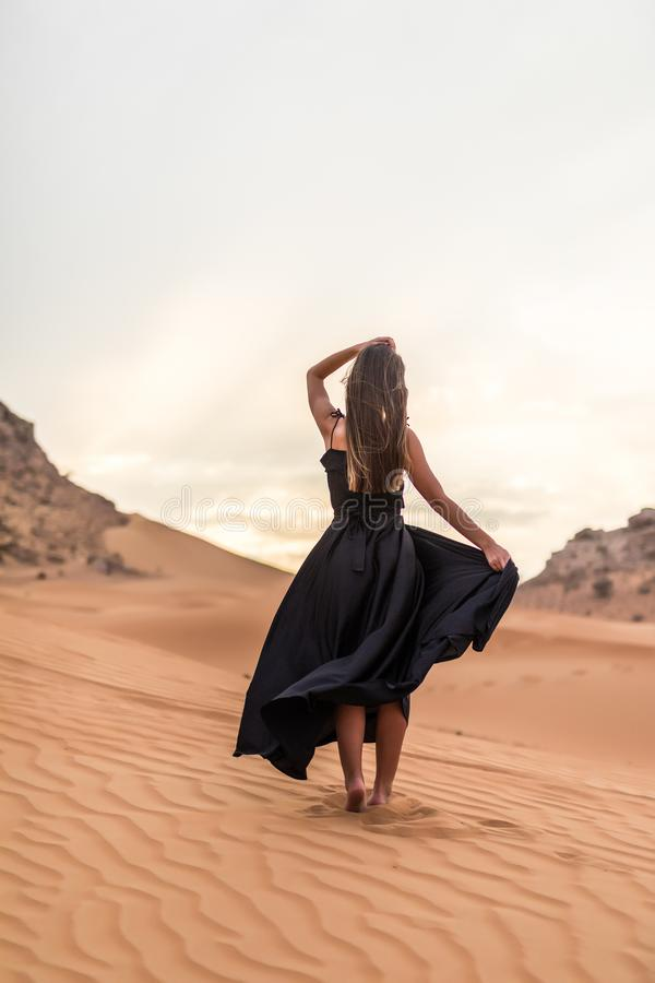 Rear view of young woman in black dress dancing in sandy desert at sunset stock images