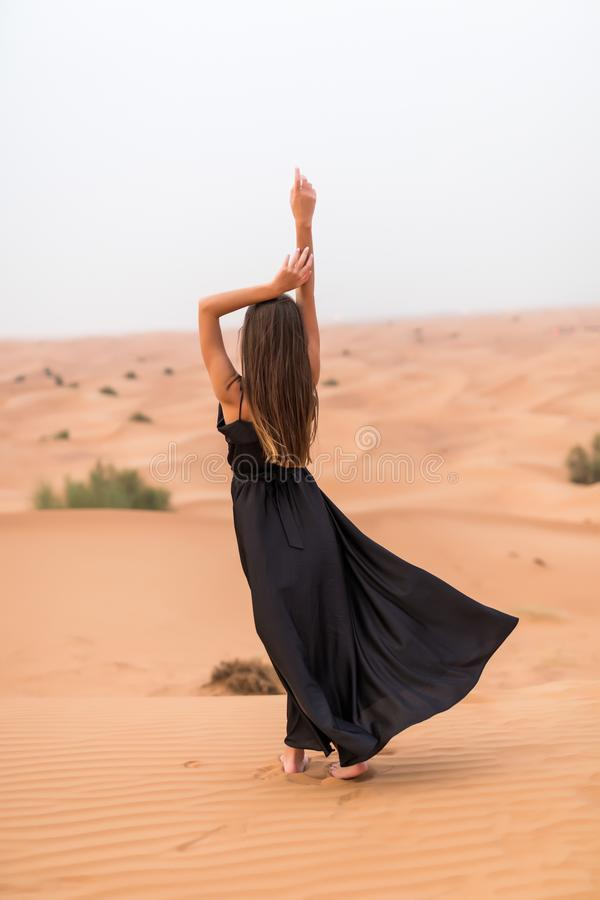 Rear view of young pretty woman in black dress dancing in sandy desert at sunset stock photo
