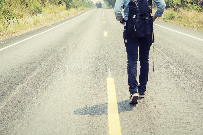 Rear view of a young woman hitchhiking carrying backpack walking. On the road stock image