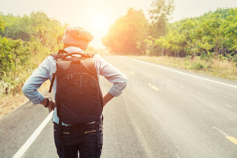 Rear view of a young woman hitchhiking on countryside road walking on the road stock images