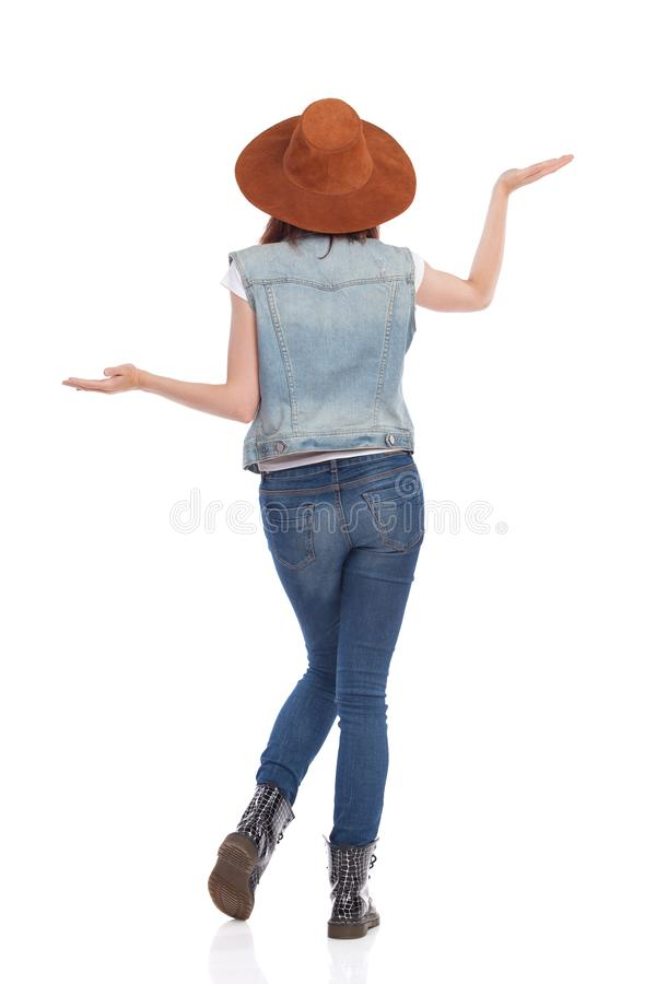 Rear View Of Young Woman In Jeans, Boots And Suede Hat With Hands Raised. Young woman in jeans vest, black boots and brown suede hat is standing with hands royalty free stock photos