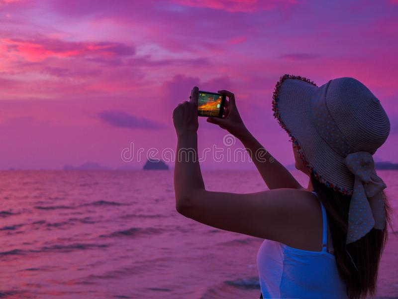 Rear view of a young woman making picture on cell telephone camera stock images