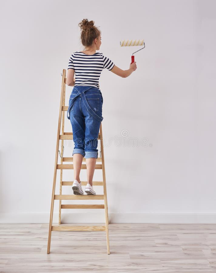 Rear view of young woman with paint roller painting wall stock photography