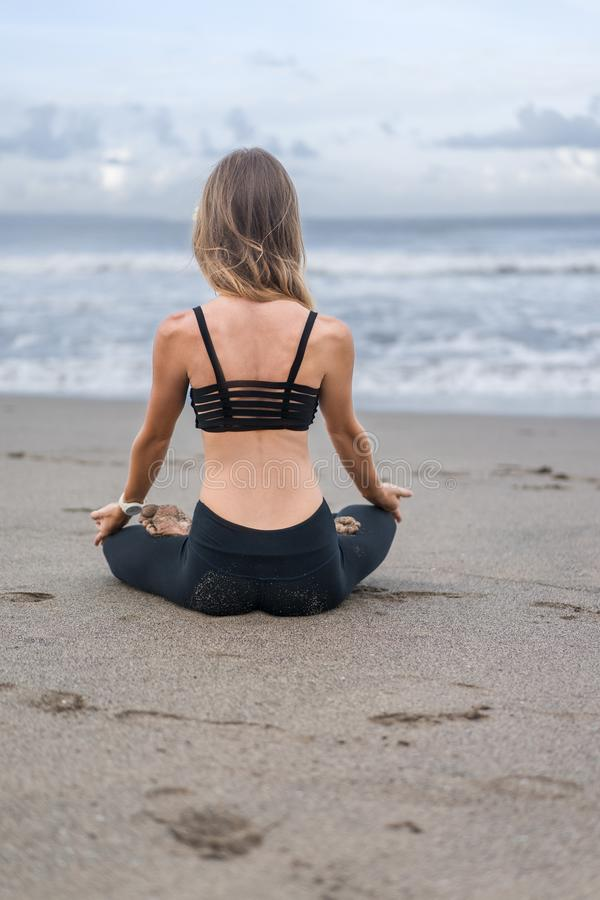 rear view of young woman practicing yoga in lotus pose on seashore royalty free stock image