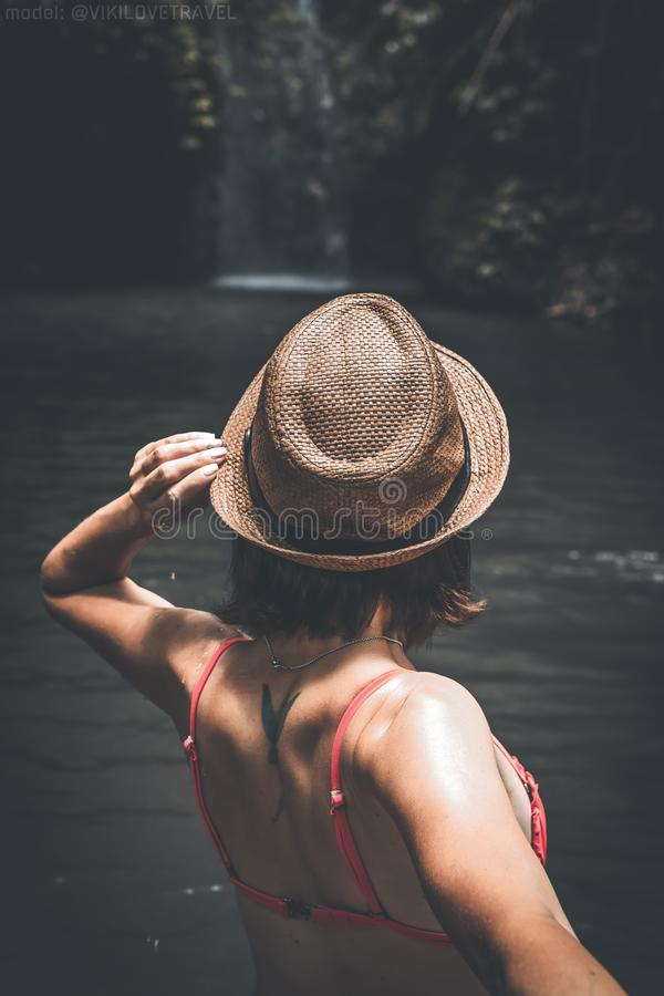 Rear view of young woman tourist with straw hat and red swimsuit in the deep jungle. Real adventure concept. Bali island. royalty free stock image