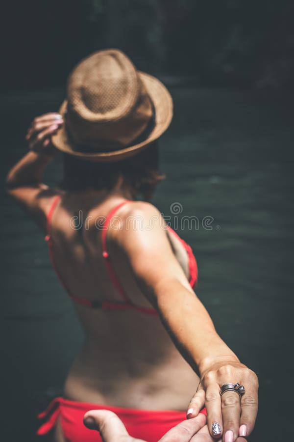 Rear view of young woman tourist with straw hat and red swimsuit in the deep jungle. Real adventure concept. Bali island. Indonesia stock images