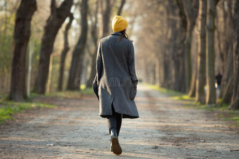 Rear view of a young woman walking on an avenue . royalty free stock photography