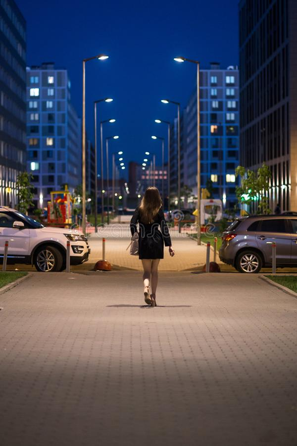 Rear view of young woman wearing black coat walking down the street, street lights towards her. A female with beautiful stock images