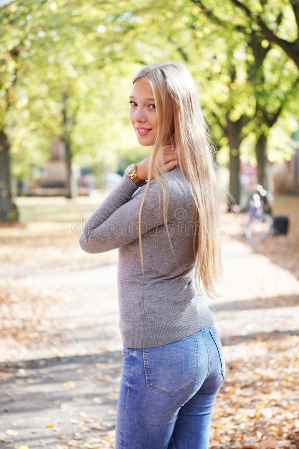 Rear view of young woman wearing jeans and sweater turning head around royalty free stock image