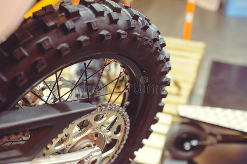 Rear wheel of motorcycle, studded tire and chain royalty free stock image