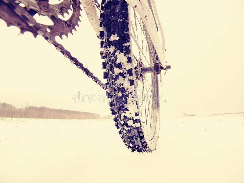 Rear wheel of mountain bicycle in snowy meadow in countryside. Detail of bike. Close-up of the rear wheel of mountain bicycle in snowy meadow in the countryside royalty free stock photos