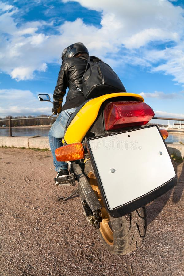 Rear, wide angle view at clear blank license plate of bike, rider sitting on motorbike royalty free stock photos