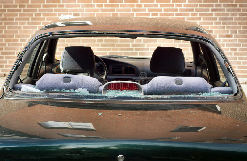 Rear window of car broken. A car on the street has been vandalized, allegedly due to a revenge act associated with street gangs wars, its rear window fully royalty free stock photography