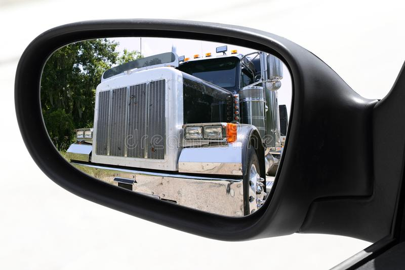 Rearview car driving mirror overtaking big truck. Lorry royalty free stock photography