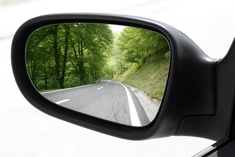 Rearview car driving mirror view forest road. Rearview car driving mirror view green forest road royalty free stock images