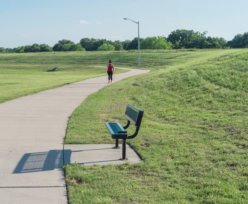 Rearview da senhora que anda no caminho com o fones de ouvido da sobre-orelha no parque verde foto de stock royalty free