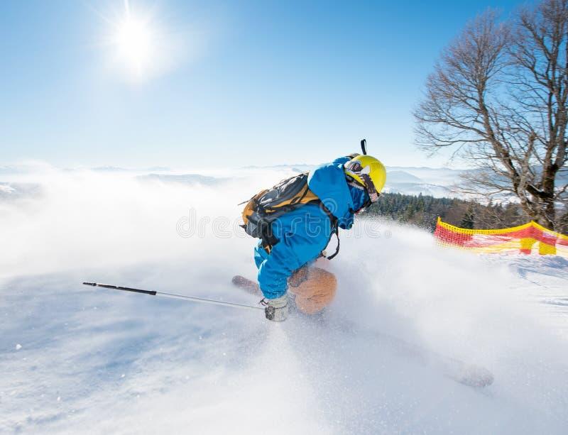 Rearview disparado de um esquiador freerider que desliza abaixo da inclinação em montanhas da estância de esqui fotografia de stock royalty free