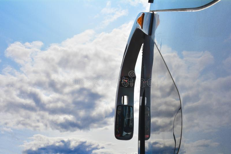 Rearview mirror in the bus. The sky in the background. Transport, blue, green, car, south, vacation, landscape, road, travel, european, roads, double, drive royalty free stock photos