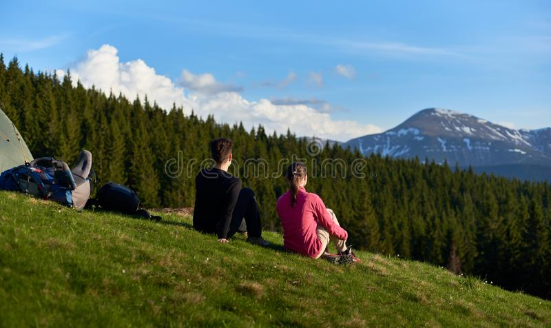 Female friends hiking together in the mountains. Rearview shot of two female hikers sitting near their tent and backpacks enjoying beautiful mountains view stock photo