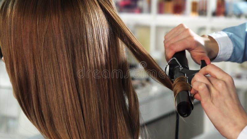 Rearview zamknięty kobieta dostaje ona włosy up fryzował fachowym hairstylist obrazy stock