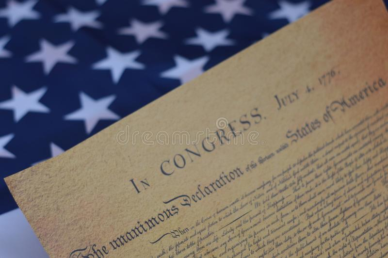 The reason behind the 4th of July. Declaration of independence laid across the star spangled banner for the forth of july royalty free stock photography