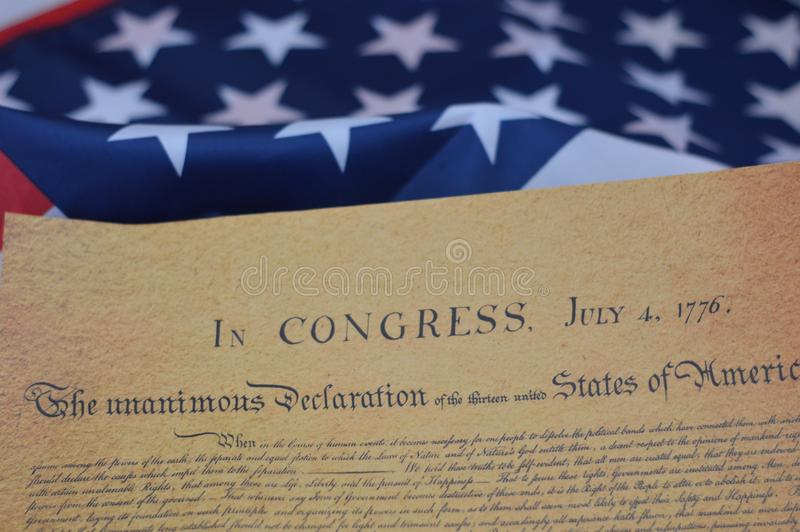 The reason behind the 4th of July. Declaration of independence laid across the star spangled banner for the forth of july royalty free stock photo