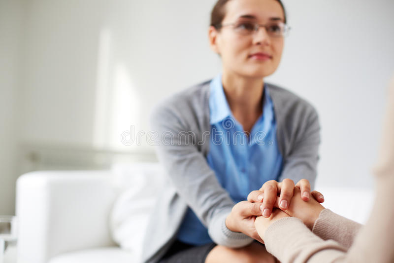 Reassuring gesture. Image of psychiatrist holding hands of her patient stock photos
