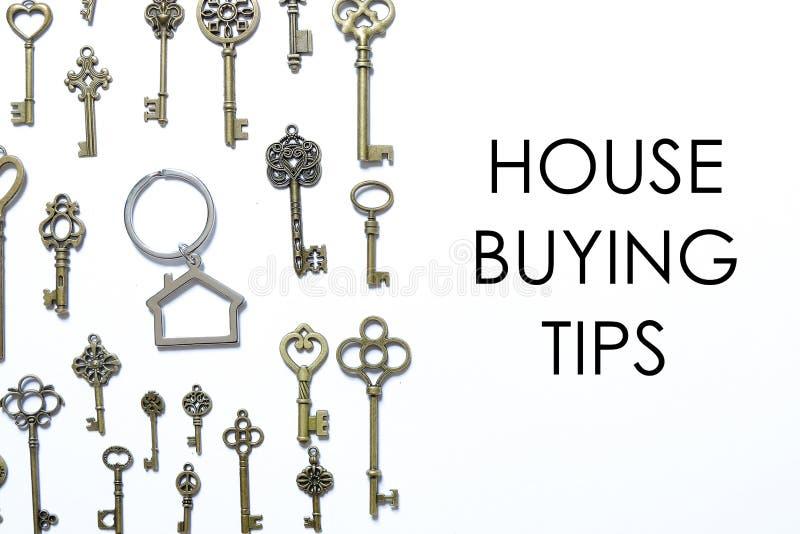 Reat nieruchomość lub własność temat Domowego kształta kluczowy łańcuch z rozmaitością klucze na białym drewnianym tle pisać z DO zdjęcia stock