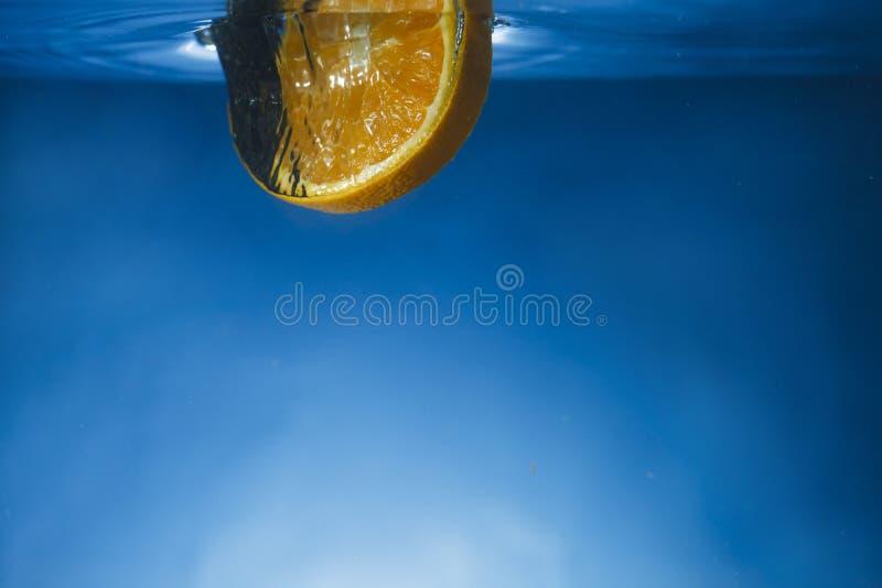 Rebanada anaranjada caída en agua cristalina imagenes de archivo