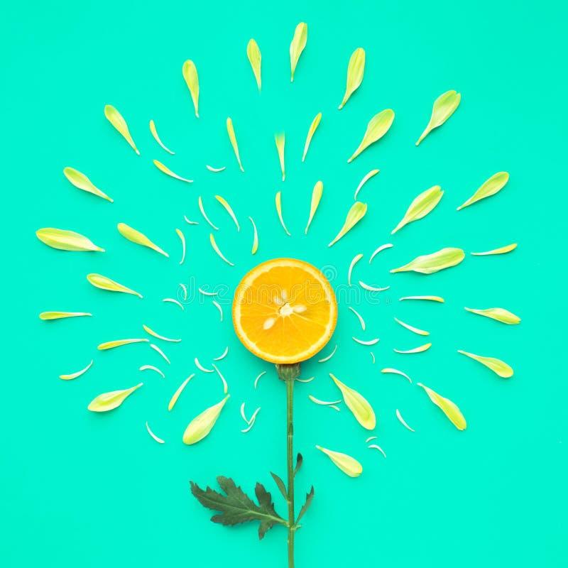Rebanada anaranjada con el pétalo de la flor en fondo verde foto de archivo libre de regalías