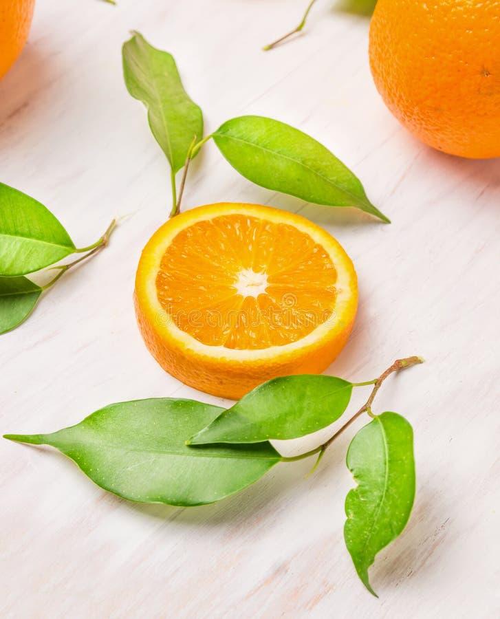 Rebanada anaranjada cruda de las frutas con las hojas verdes imagen de archivo