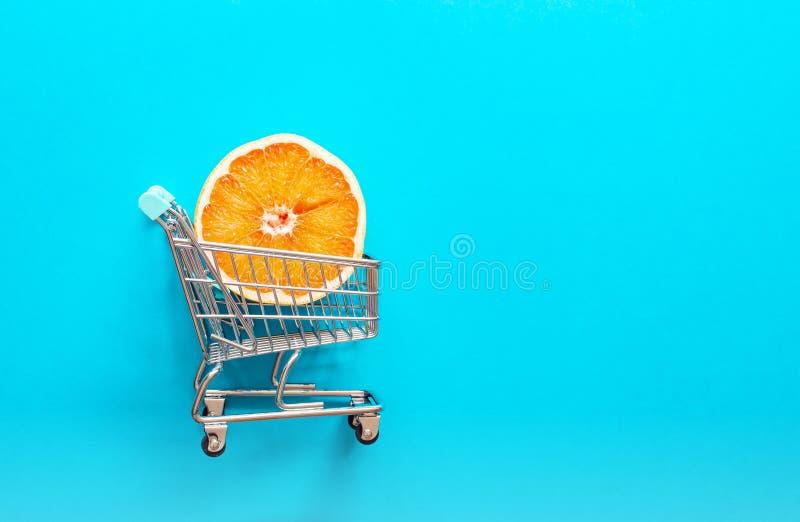 Rebanada anaranjada roja del pomelo en mini carretilla en el fondo azul, endecha plana imagenes de archivo